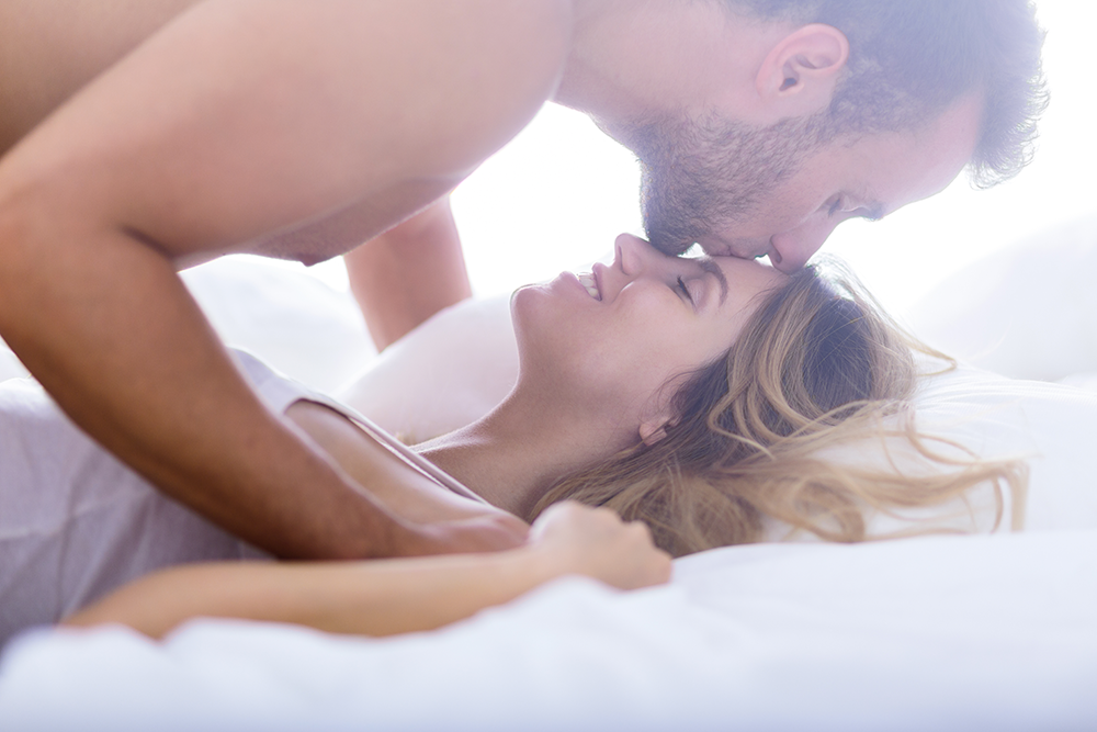 Couple kissing in bed Allure Chattanooga